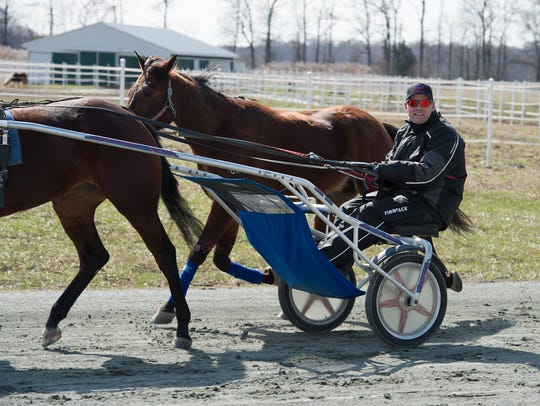 Steven Nason of Freedom, New Hampshire, on the practice track with Monkey and Geremel Hanover, at Track View Farm in Hartly.