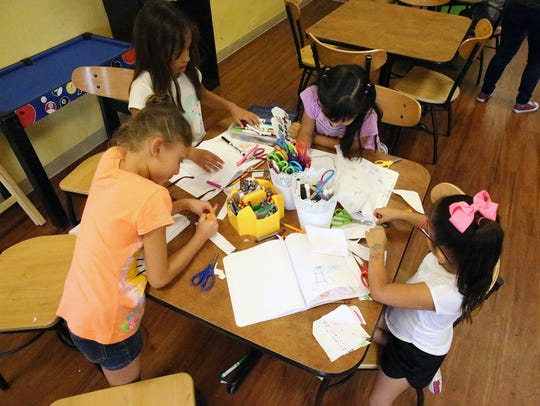 Young girls do arts and crafts at the Boys and Girls