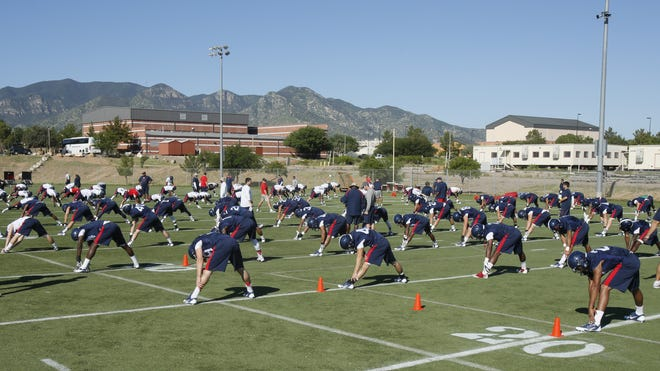 The Arizona football team stretches in the shadow of the Huachuca  Mountains during its first day of practice at Fort Huachuca on Aug. 8, 2013 in Tucson.