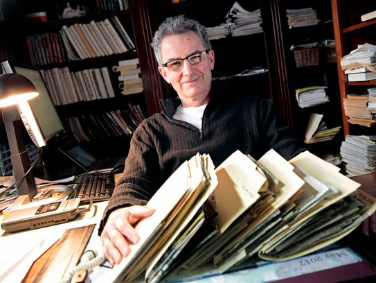 Bob McGinn sits in his home office with some of his