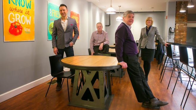 John Hawkins (second from right), president and chief executive officer of ab+c Creative Intelligence, retires from the company as he's joined by managing partners (from left) Paul Pomeroy, Tom McGivney and Linda Shopa.