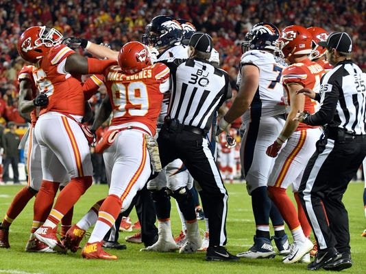 Officials try to break up a scuffle between Kansas City Chiefs and Denver Broncos players during the first half of an NFL football game in Kansas City, Mo., Monday, Oct. 30, 2017. (AP Photo/Ed Zurga)