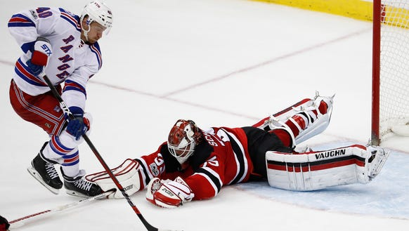 New Jersey Devils goalie Cory Schneider, right, dives