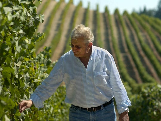 Don Carano inspects grape clusters in a RockRise Mountain