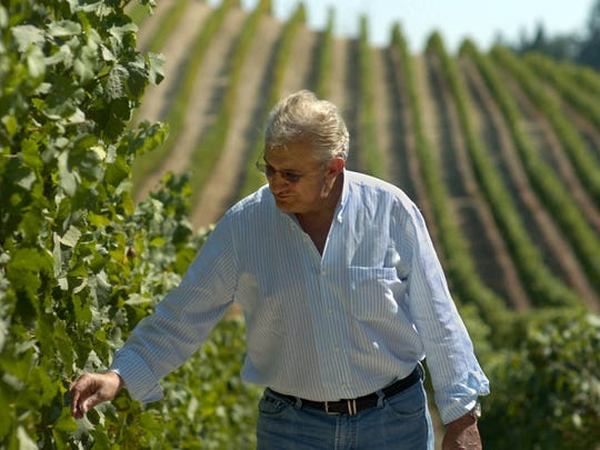 Don Carano inspects grape clusters in a RockRise Mountain vineyard a few weeks before the 2006 harvest.