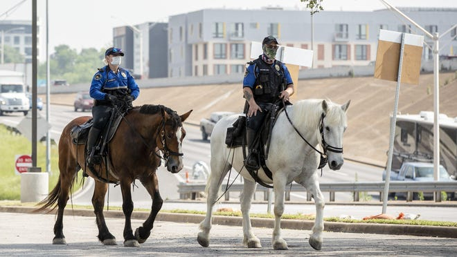Austin police officers wear masks while they patrol downtown on horseback.