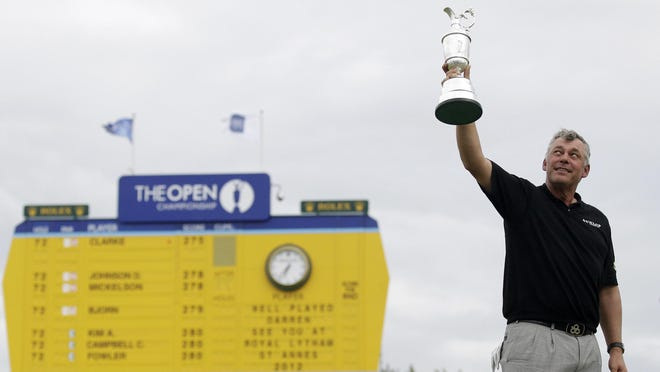 Northern Ireland's Darren Clarke holds up the Claret Jug trophy on the 18th green as he celebrates winning the British Open Golf Championship at Royal St George's golf course Sandwich, England, where the 2020 Open was to be held until coronavirus canceled the tournament.