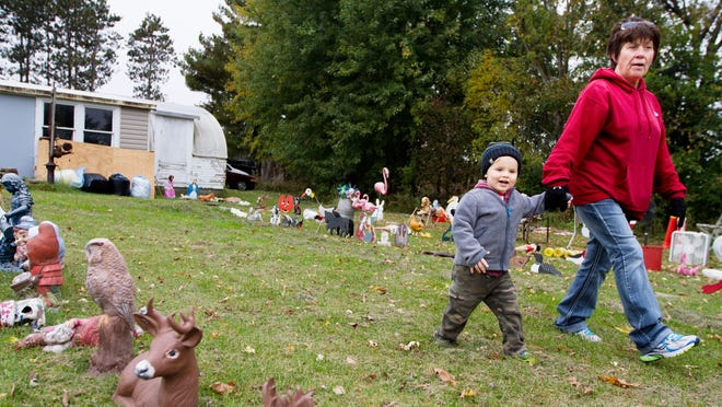 Sylus Denning walks with his baby sitter Karen Maas through rows of lawn ornaments to be auctioned from Darold Mayer's yard southeast of Eau Claire. Mayer, 82, is in the process of selling the property and moving to Eau Claire.
