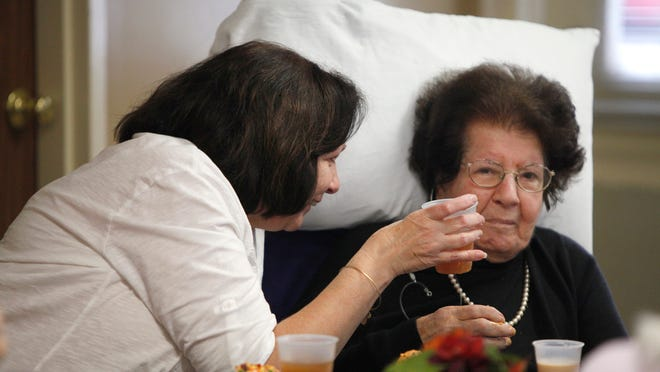 Susan Andrews offers her mother, Catherine Megalo, a drink during entertainment at Latta Road Nursing Home, where Catherine lives.