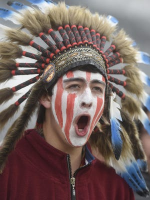 """In this May 20, 2015, file photo, a Cheyenne Mountain High School student wears a headdress and face paint as he cheers for his school -- which uses """"Indians"""" as its team mascot -- in the 4A State Soccer Championship game at Dick's Sporting Goods Park in Commerce City, Colo."""