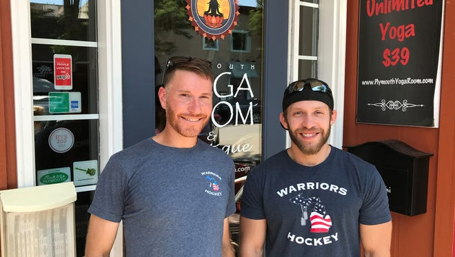 Mike McTaggart (left) and Josh Krajewski of the Michigan Warriors military veterans hockey team are all smiles after receiving a check for $850 from Michigan Yoga Room in Plymouth. The yoga studio had a July 4 fundraiser for the hockey organization.