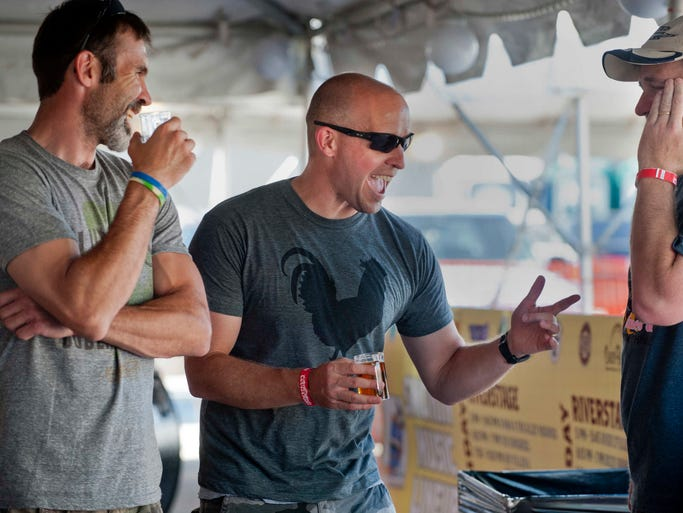 """L-R: Chris Jochem, Aaron Songer and John Schroeder, members of the Rest In Pork (RIP) barbecue team and childhood friends, all from Huntingburg, In., joke with each other at the People's Choice contest of the 6th annual """"Smokin' on the River"""" BBQ, Blues and Brew Festival. 13 June 2014"""