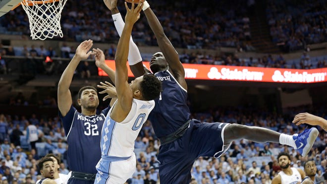 North Carolina's Nate Britt (0) is blocked by Monmouth's Pierre Sarr and Diago Quinn (32) during the first half of an NCAA college basketball game in Chapel Hill, N.C., Wednesday, Dec. 28, 2016. (AP Photo/Gerry Broome)