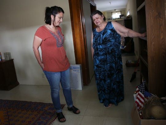 Maria Friske, left, talks with Lillian Gonzales in her home after Friske delivered a fan for Gonzales to help her keep her apartment cool during the summer.