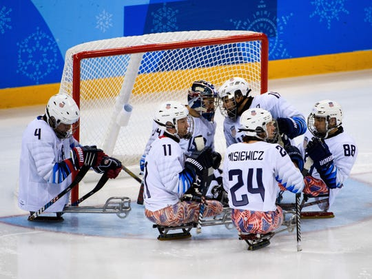 USA sled hockey team members, including No. 11 Tyler Carron of Fort Collins, gather at the net during a Paralympic Winter Games preliminary round game against Czech Republic on Monday in PyeongChang, South Korea.