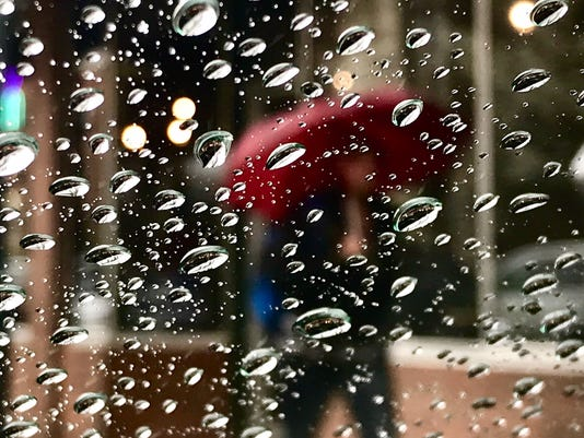 Rain falls over downtown Reno as man walks with umbrella