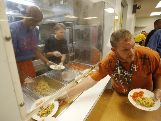 Volunteer Eric Whetstone (center) mans the food line with resident workers Leroy Wyatte (left) and Brad Kozakowski as they distribute meals Friday evening at the Sunday Breakfast Mission in Wilmington.