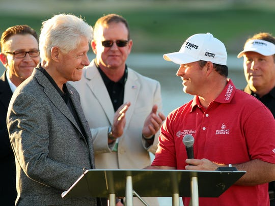 Operation Iraqi Freedom veteran, amputee, and amateur golfer Chad Pfeifer (right) introduces former President Bill Clinton during the Humana Challenge Military Appreciation Ceremony on Saturday.
