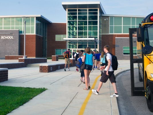 Spring Grove Area School students get off the bus Wednesday as the sun rises. ( YORK DAILY RECORD/SUNDAY NEWS -- PAUL KUEHNEL )