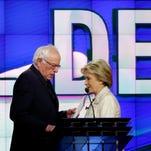 Bernie Sanders and Hillary Clinton pass during a break at a CNN debate Thursday, April 14, 2016 in New York.