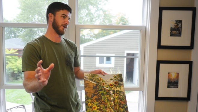 Watercolorist Dan Mondloch talks about his favorite painting at his home Monday in St. Cloud. Mondloch spent three days painting the sunflowers in his backyard.