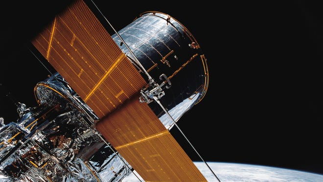 In this April 25, 1990, photograph provided by NASA, most of the giant Hubble Space Telescope can be seen as it is suspended in space by Discovery's Remote Manipulator System (RMS) following the deployment of part of its solar panels and antennae. This was among the first photos NASA released on April 30 from the five-day STS-31 mission.