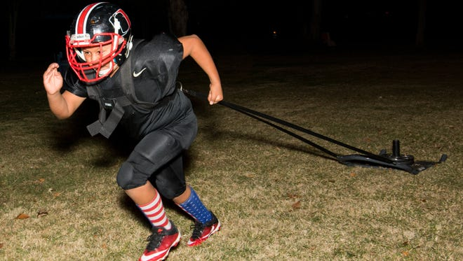 Bandido Nerf League Football player, nine year old Xander Parra pulls the dragging sled during conditioning drills on November 10, 2016.