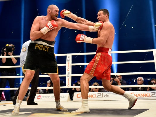 FILE - In this Nov. 29, 2015, file photo, Ukraine's Wladimir Klitschko, right, and Britain's Tyson Fury exchange blows during a boxing bout in Duesseldorf, western Germany. Fury won the bout. During Klitschko's rein as champion, every opponent was kept at arm's length. Punches were traded cautiously _ probably with good reason, considering what Lamon Brewster did to him back in 2004. Klitschko never won any style points, though he kept winning against a series of opponents who could never seem to crack the code. Then Fury entered the picture, making Klitschko look slow and old in breaking his 11-year winning streak to win his heavyweight titles. Now Klitschko challenges the unbeaten Anthony Joshua for the title. (AP Photo/Martin Meissner, File)