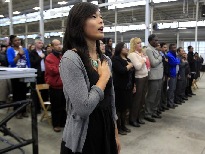 Sohee Michell Kwon, 18, originally from South Korea, leads the Pledge of Allegiance as the youngest citizen during the naturalization ceremony, Friday, November 22, 2013, at the Indiana State Fairgrounds. More than 200 new Americans were sworn in as citizens as part of the 37th annual Indy International Festival.