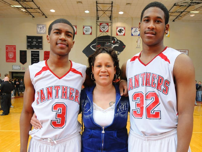 North Central High School's Ronnie Johnson (3), and his older brother, Terone Johnson (32), pose with their mother Rona Johnson after the pair's game Saturday night.  North Central High School hosted Danville High School in a match-up of top-ranked teams Saturday evening, February 20, 2010. North Central defeated Danville 76-63, giving the Warriors their first loss of the season.