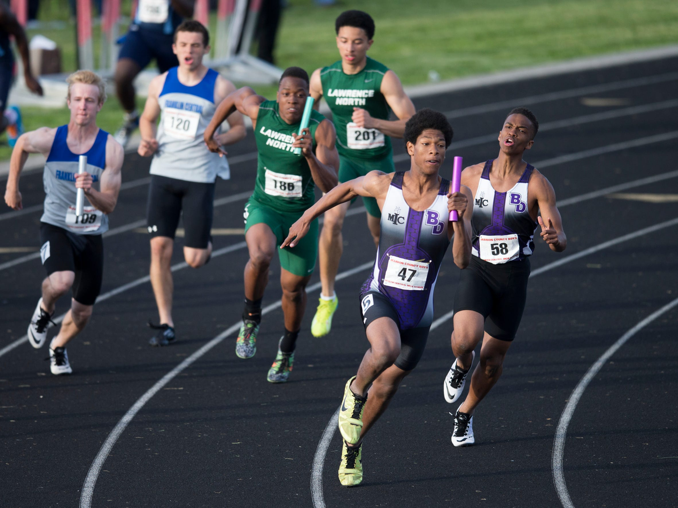 Christian Powell (47), of the Ben Davis High School team, heads out on the final leg after taking a handoff from Rodney Williams, during their winning 4 X 100 meter effort, boys marion county track meet, Indianapolis, Wednesday, May 13, 2015.