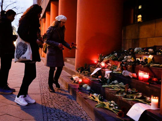 Women lay flowers in front of the Belgium Embassy in