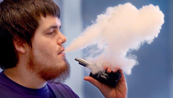 Josh Maynard, an employee at Indy Vapor Shop, takes a break to smoke his e-cigarette.