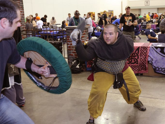 Grant Walker, right, battles Mike Stocks with foam swords during Gen Con Friday, August 15, 2014, afternoon at the Indiana Convention Center.