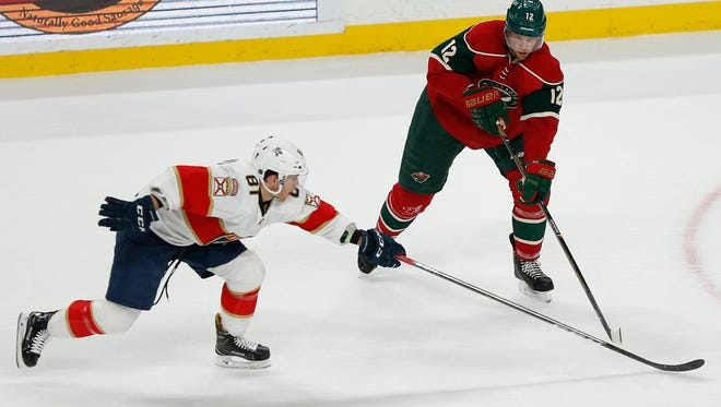 Minnesota Wild's Eric Staal (12) passes the puck around Florida Panthers' Jonathan Marchessault (81) in the third period of an NHL hockey game Tuesday, Dec. 13, 2016, in St. Paul, Minn. The Wild won 5-1. (AP Photo/Stacy Bengs)