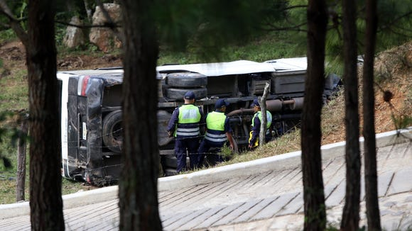 This photo courtesy of El Heraldo de Honduras newspaper shows a bus on its side along the highway between the town of San Juancito and the capital city of Tegucigalpa, Honduras, Wednesday, Jan. 13, 2016. Two New York college students and a U.S. health-care worker died Wednesday in this Central American nation when their bus crashed while taking them to the airport to fly home after a volunteer mission helping poor Hondurans. (El Heraldo de Honduras via AP) ORG XMIT: HND101
