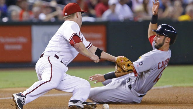 Arizona Diamondbacks third baseman Aaron Hill (2) can't get the tag on St. Louis Cardinals' Matt Carpenter (13) as he advances to third on a single by Thomas Pham during the first inning of their MLB game Tuesday, August 25, 2015 in Phoenix, Ariz.