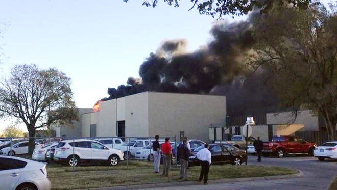 Black smoke billows from a building at Mid-Continent Airport where officials say a plane crashed Thursday, Oct. 30, 2014 in Wichita, Kan.