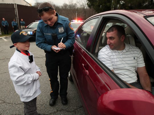 Ptl. Nicole Sorgie helps 6-year-old Thomas DeChristofano of Roxbury write up a warning to passenger Detective Jack Sylvester. Thomas and his brother James both won a chance to ride with Roxbury police and pulling over two Detectives, issuing them a warning for not wearing a seatbelt. December 16, 2015, Roxbury, NJ.