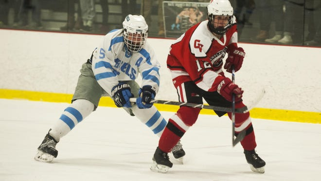 South Burlington's Michael Flaherty (5) battles for the puck with CVU's Joe Parento (12) during the boys hockey game between the Champlain Valley Union Redhawks and the South Burlington Rebels at Cairn's Arena on Wednesday night February 3, 2016 in South Burlington.