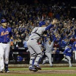 New York Mets' Wilmer Flores walks off the field after striking out as Kansas City Royals catcher Drew Butera celebrates after Game 5 of the Major League Baseball World Series on Monday in New York. The Royals won 7-2 to win the series.