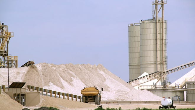 Trucks move frac sand toward a processing plant in this file photo from western Wisconsin. Sand plants are laying off workers amid a crash in oil prices brought about by the COVID-19 pandemic.