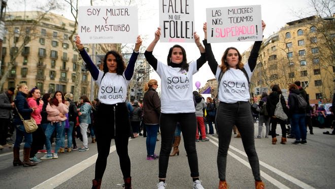 Three women hold up placards as they attend a demonstration during a one day strike to defend women's rights on International Women's Day in Barcelona, on March 8, 2018.