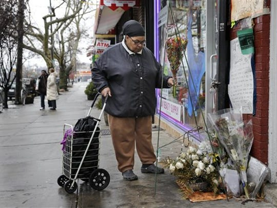 A woman, who did not want to give her name, places flowers at a memorial for Eric Garner near the site of his death in the borough of Staten Island.