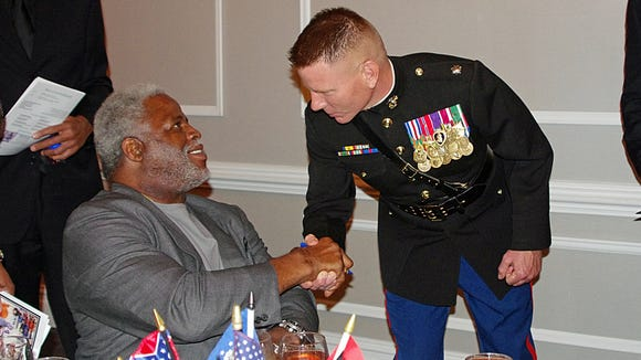 Football legend Earl Campbell shakes hands with retired U.S. Marines Lt. Col. J.D. Harrill, who served three tours of duty in Afghanistan and Iraq.