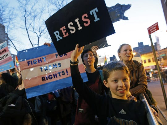 Tal Moskowitz, 8, below, a transgender child, holds a sign as his parents Faigy Gelbstein, left, and Naomi Moskowitz, upper right, of Long Island, hold separate signs during a rally in support of transgender youth at the Stonewall National Monument, Thursday, Feb. 23, 2017, in New York. They were among demonstrators The crowd gathered Thursday night in front of the Stonewall Inn. The family were speaking out against President Donald Trump's decision to roll back a federal rule saying public schools had to allow transgender students to use the bathrooms and locker rooms of their chosen gender identity. The rule had already been blocked from enforcement, but transgender advocates view the Trump administration action as a step back for transgender rights. (AP Photo/Kathy Willens)