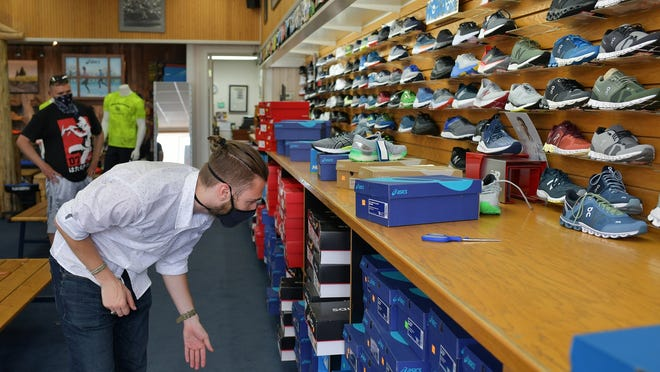 Jackson Genatossio looks for a pair of sneakers for a customer at Sneakerama in Worcester, which was open for business Tuesday.