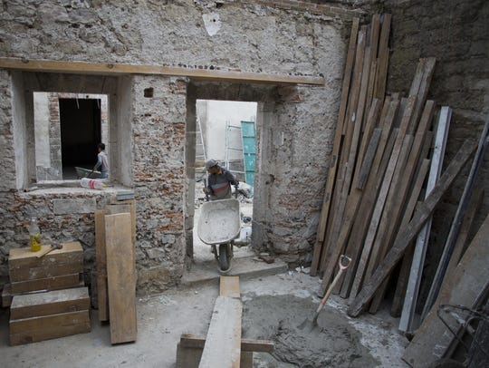 A mason pulls a wheelbarrow inside the building of