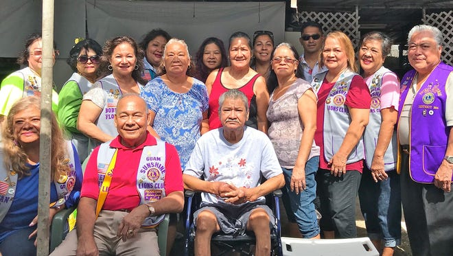 """The Guam Sunshine Lions Club, in serving the community and fulfilling its mission of """"Caring for the Sick and the Elderly,"""" donated a transport chair and a shower bench to Agat resident Vicente Salas, 68, during a home visit on March 24. Lunch provided by the Salas family followed the presentation. Seated from left: Lions LouJean and Pete Babauta; and Vicente Salas. Standing from left: Lions Clare Cruz, Connie Rivera, and Bobbie Flores; Florence Borja, Frances Dudkiewicz, and Florence Salas; Lions Julie Cruz, Dee Cruz, Danny Cruz, and Marietta Camacho. Back row from left: Lions Lorraine Rivera, Julie Garcia, and Tish Tano; and Daniel Salas."""