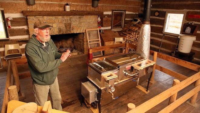 Bruce Warthen explains how maple tree sap is collected then reduced to syrup in the propane fired evaporator in the log cabin at Dawes Arboretum.